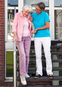 Care assistant helping a senior lady on steps holding her hand as they descend a set of wooden stairs outdoors on the care home in Springfield MO