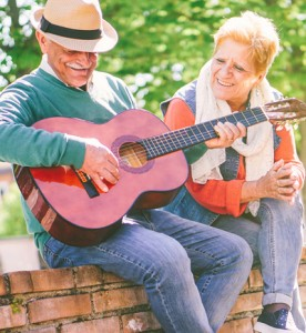 Happy senior couple playing a guitar while sitting outside on a wall on a sunny day - Concept of active elderly having fun with guitar - Enjoying lifestyle during retirement in Palm Beach and Broward Counties FL