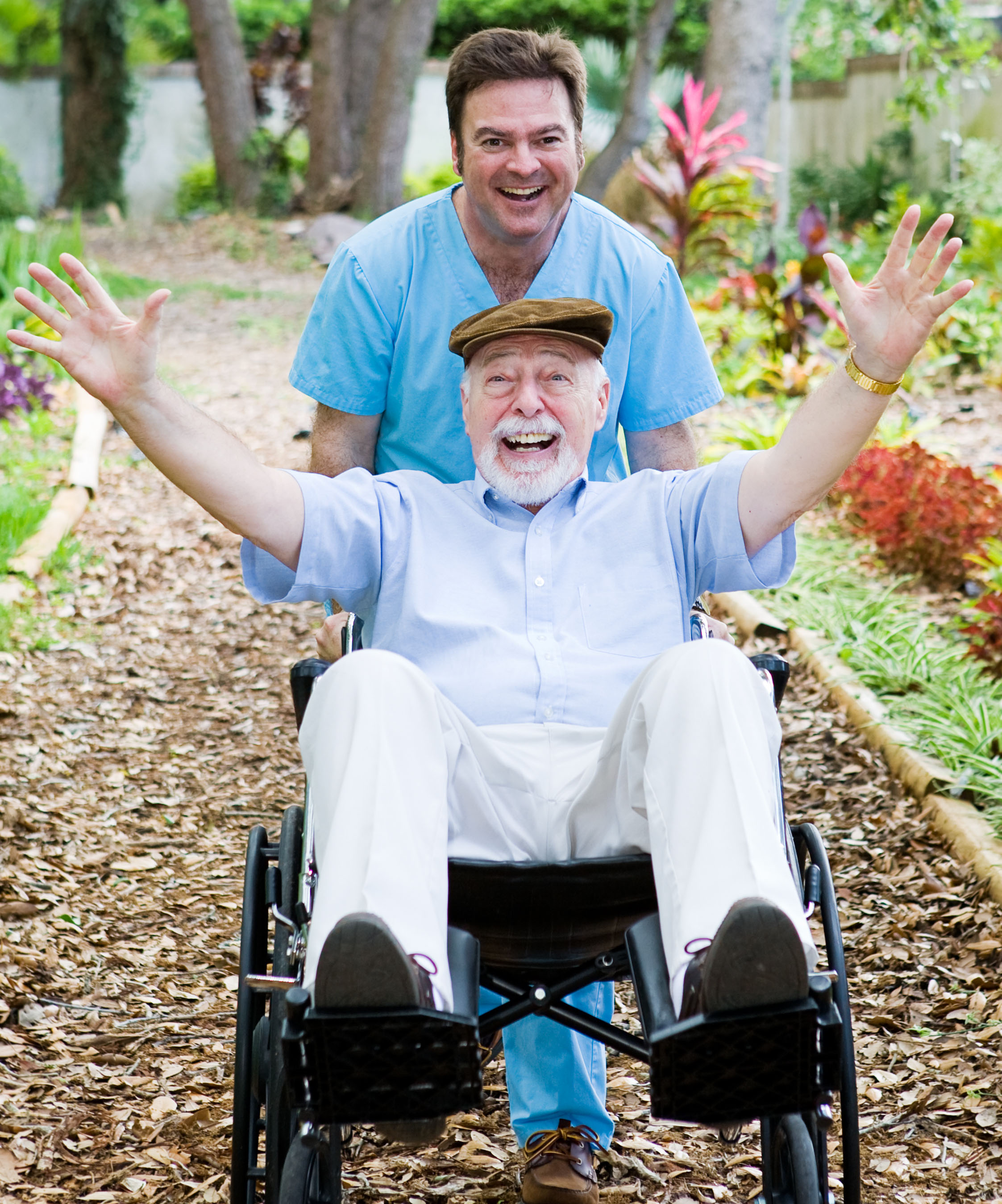 Caring nursing home orderly pops a wheelie with an elderly man's wheelchair. They are having fun in Chicago North